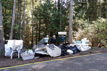 Community volunteers stand with some of the debris removed from Mayne Island beaches in 2018